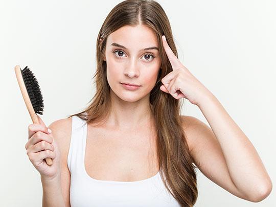 mulher branca com cabelos castanhos segurando uma escova com a mão direita e com a mão esquerda aponta para a cabeça