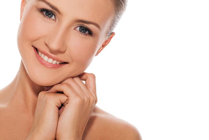 No canto esquerdo da imagem está uma mulher branca de olhos azuis, com cabelos castanhos, presos em um coque. Ela está sorrindo e apoia sua cabeça para a direita da imagem sob as suas mãos. O fundo da imagem é branco.