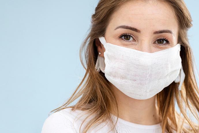 A imagem mostra uma mulher branca, de cabelo castanho claro, curto e ondulado, e olhos castanhos. Ela está posicionada à esquerda da imagem e usa máscara de proteção branca na face e blusa branca. O fundo da imagem é azul claro.