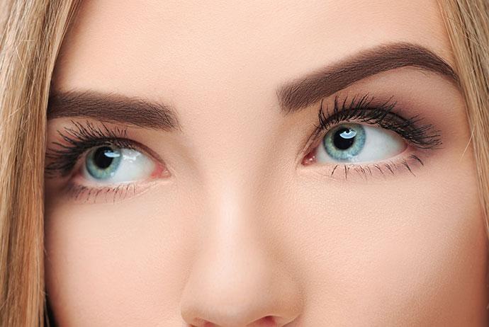 Imagem em close a região dos olhos de uma mulher branca, loira, de olhos azuis. A mulher tem cabelos lisos, sobrancelhas na cor castanho e está com os olhos voltados para a esquerda da imagem.