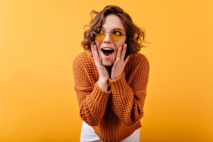 Uma mulher branca, com cabelos curtos e castanhos, está levemente inclinada para frente e com as mãos ao lado das bochechas. Seu semblante é de surpresa, com a boca aberta e olhos arregalados. Ela usa um blusão de tricô caramelo, calça branca e óculos redondos com lentes amarelas. O fundo da imagem é amarelo.