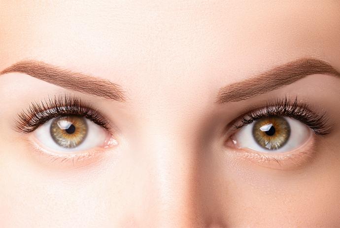 A imagem mostra, em close, os olhos de uma mulher branca, de olhos verdes e sobrancelhas castanho-claro.