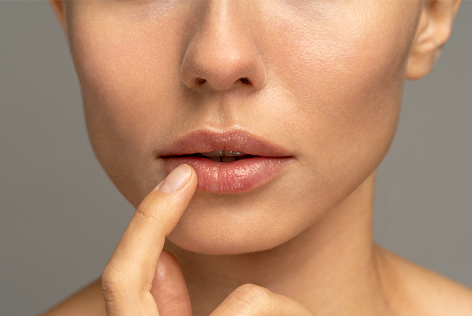 A imagem mostra, em plano fechado, a região entre o nariz e o pescoço de uma mulher branca. Ela está posicionada de frente e seu dedo indicador direito toca seu lábio inferior. O fundo da imagem é cinza.